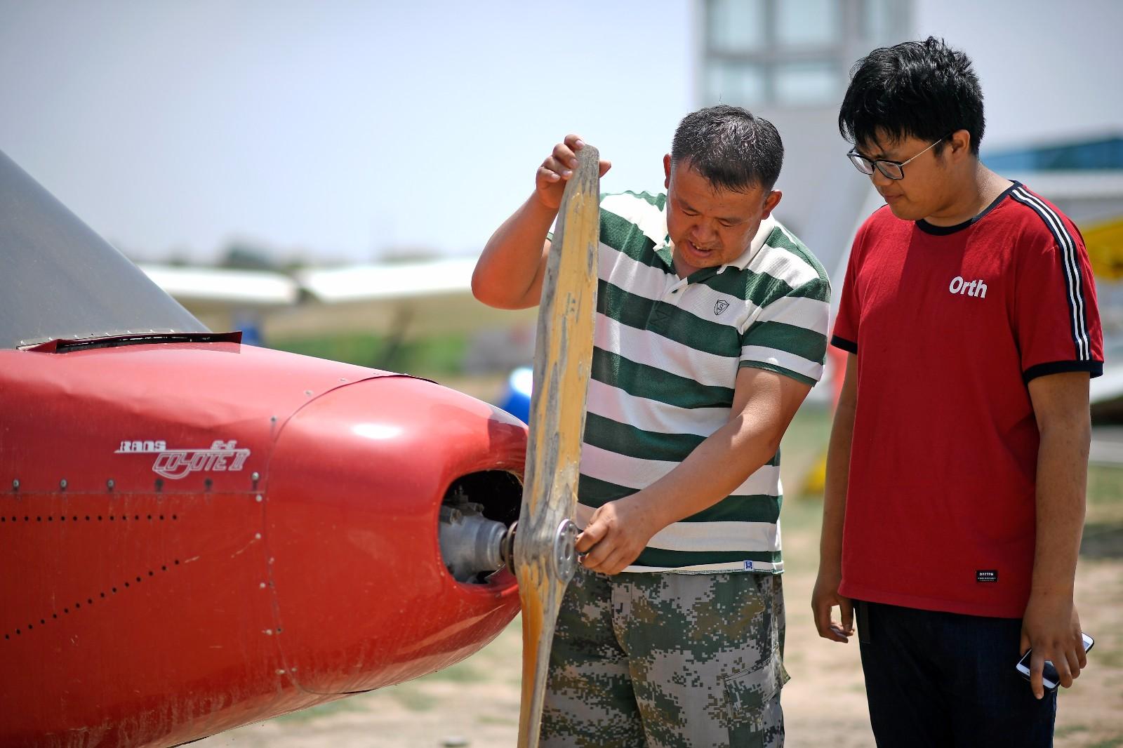 刘亦兵(左)在飞行营地与儿子交流飞机技术知识(6月21日摄)。
